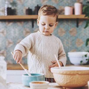 Pojke i köket lagar mat
